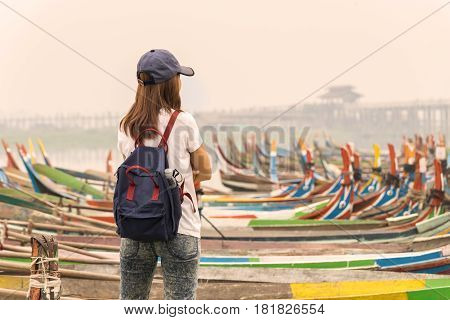 Young women traveler looking at U bein bridge. The longest wooden bridge in Mandalay Myanmar