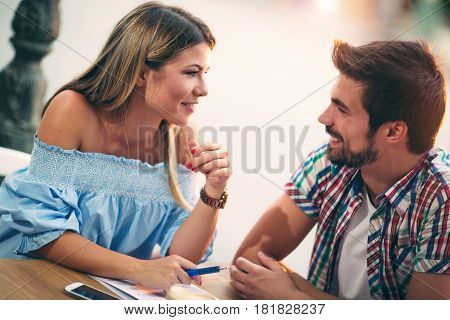 Young couple sitting in a cafe talking and enjoying on the first date