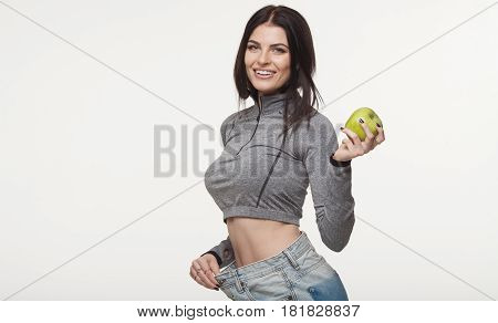 Rear view of a happy woman who lost a lot of weight against white background