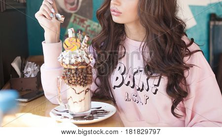 A beautiful woman drinking milk shake and whipped cream on the top with straw in vintage cafe