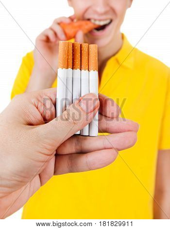Young Man with Carrot refuse a Cigarette Isolated on the White Background
