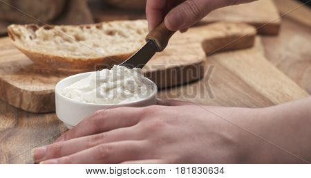 taking ricotta cheese to spread on bread, 4k photo