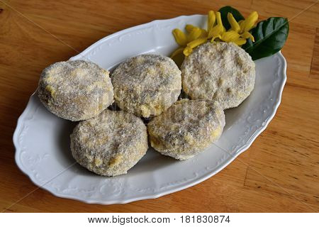 Champignons stuffed with a mixture of cheese and sausage on a plate covered with in bread crumbs and flour.