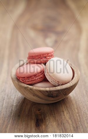 pastel colored macarons with strawberry and rose flavour in wood bowl on table