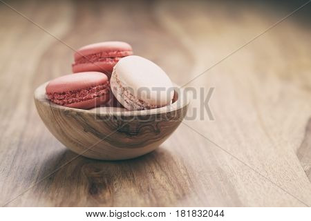 pastel colored macarons with strawberry and rose flavour in wood bowl on table vintage toned