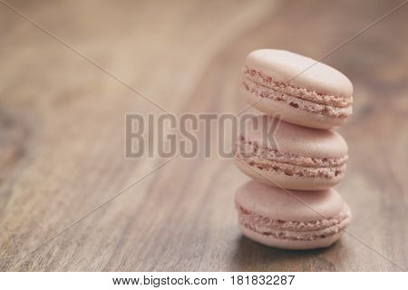 closeup shot stack of pastel colored macarons with rose flavour on wood table, vintage toned photo
