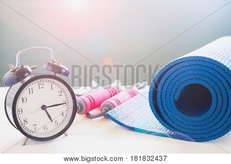 Sport and yoga equipments with alarm clock Workout and healthy lifestyle concept with copy space