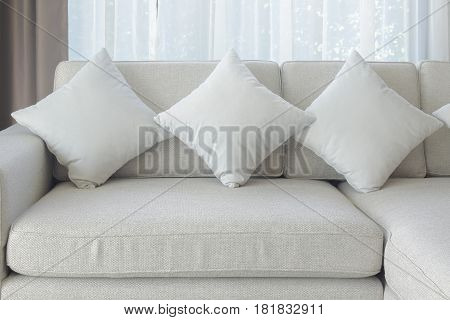Pillows And Sofa In Beige Color With Sheer Curtain In Background