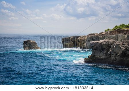 Blue ocean meets rocky cliffs in the distance, cloudy sky and greenery in the background. Ceningan Island, Bali.