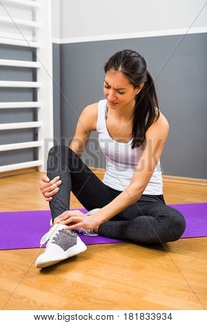 Young woman has got sport injury at the gym.