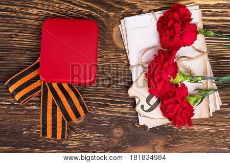 George's ribbon on the table with three carnations and letters