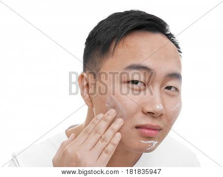 Young Asian man applying cream for problem skin onto face, on white background
