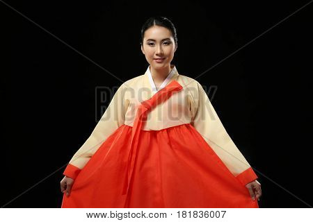 Beautiful young woman dressed in traditional clothing on black background