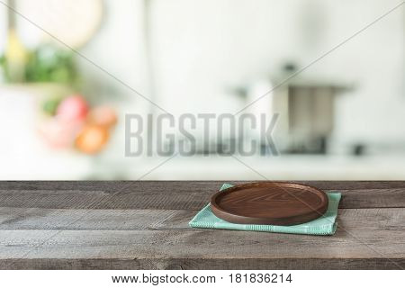 Blurred and abstract background. Empty wooden tabletop with tray and defocused modern kitchen background for display or montage your products.