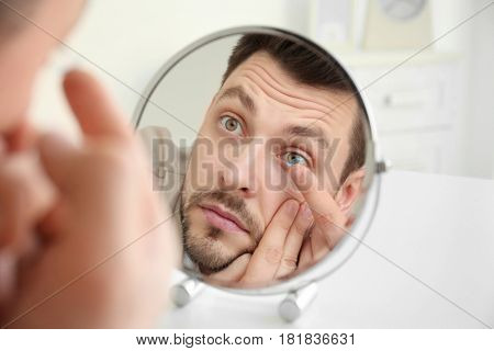Young man putting contact lenses in front of mirror at home