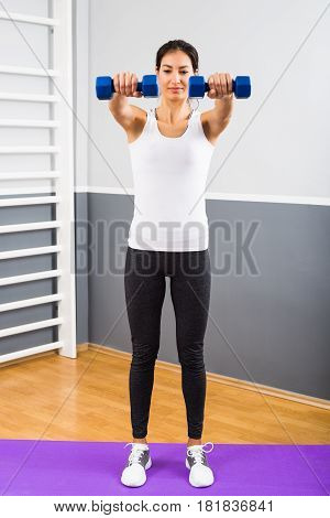 Beautiful young woman exercising with weights at the gym.