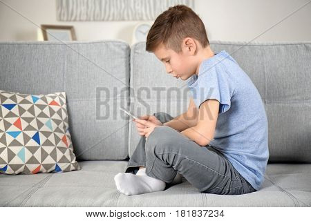 Incorrect posture concept. Schoolboy with phone sitting on sofa