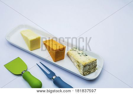 A selection of cheese's on a board with cheese cutting tools