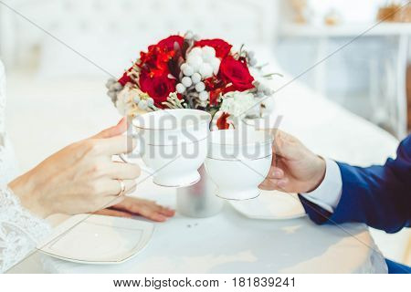 The hands of the bride and groom hold cups