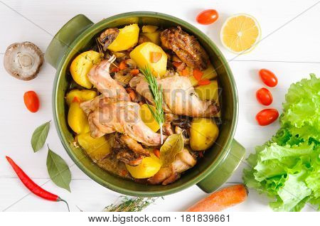 Top flat view of roasted rabbit meat with vegetables and herbs in round ceramic pot on white wooden table surface