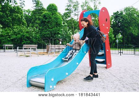 Little Boy Child playing on a playground. Happy family on playground in summer or springtime in a park. Leisure childhood and people concept