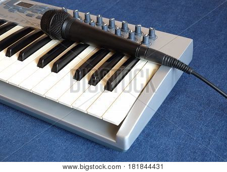 Black microphone on electronic synthesizer keyboard with many control knobs on denim background side view closeup
