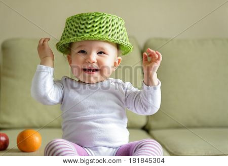 Cheerful baby girl plays with dish and fruit at home. A child holds up his hands.