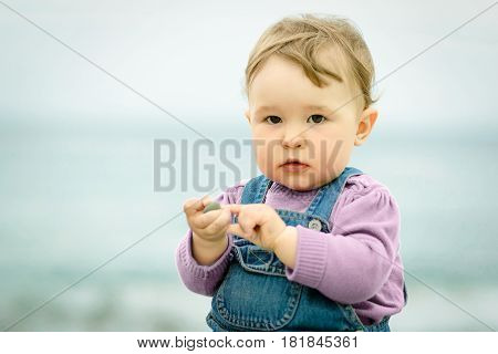 Cute one-year old baby plays with pebbles and looks at the camera on the beach