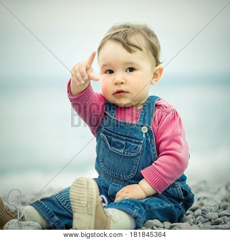 Cute baby playing with pebbles on the beach. The one-year child points his finger.
