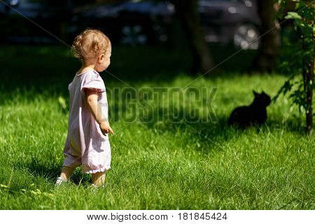Cute baby girl goes for a black cat in the park. One-year child plays on the lawn.
