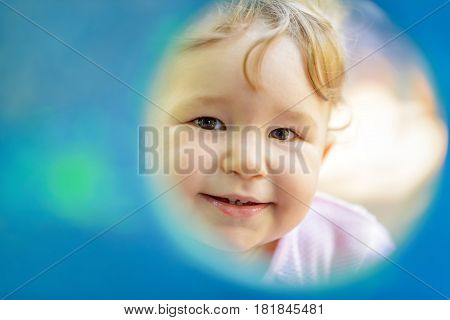 The one-year child plays on the playground. Cute baby girl looks through a round window to the camera.