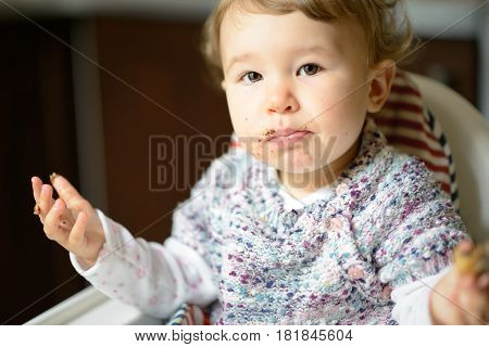 Eating baby girl with messy face. The nice one-year child eats and looking at the camera.