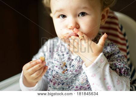 Eating baby girl with messy face. The one-year child eats and puts fingers in his mouth and looking at the camera.