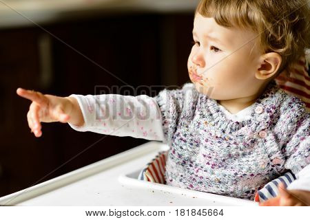 Eating baby girl with messy face and full mouth of food. The one-year child points his finger demanding more food.