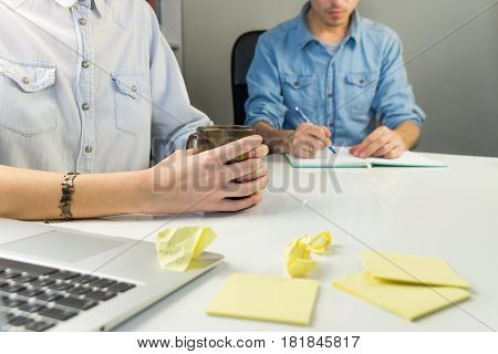 Two persons working at white modern office desk. Male and female coworkers sit at modern home office working place, male human take notes in book