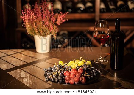 Composition of wine bottle, glass fruits and flower pot placed on a wooden table in a wine vault.