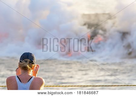 Tourist photographing the lava pouring into the sea in Volcanoes National Park, Big Island, Hawaii
