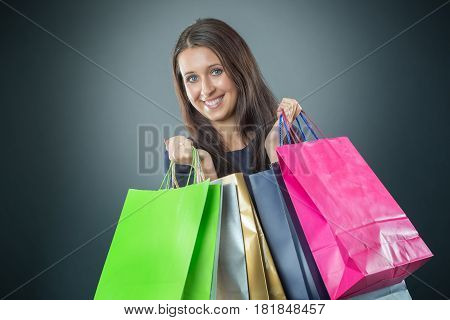 Portrait of young happy smiling woman with shopping bags credit card and shoes.