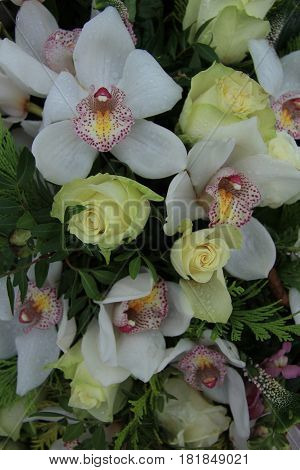 Cymbidium ochids and roses in a white bridal arrangement