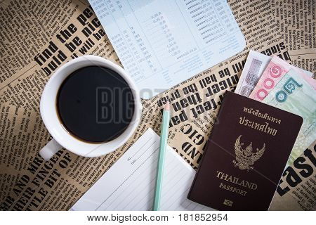 Thailand Passport with currency Coffee and Glasses on a text Background.
