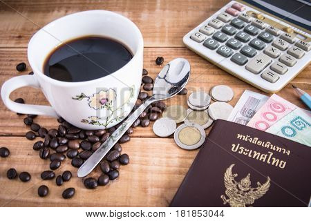 Thailand Passport with currency Coffee and Glasses on a Wood Background.
