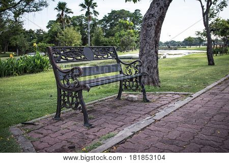 Metal garden chair on rock ground with green grass