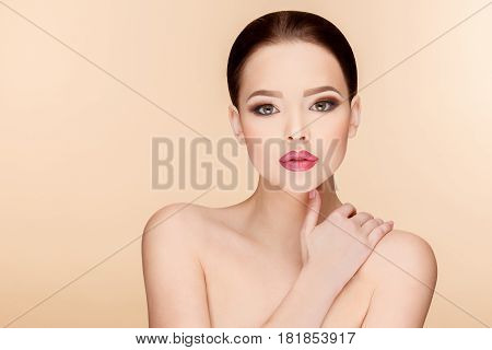 Beautiful Face of Young Woman with Clean Fresh Skin close up on beige background. Beauty Portrait. Beautiful Spa Woman Smiling. Perfect Fresh Skin. Pure Beauty Model. Youth and Skin Care Concept