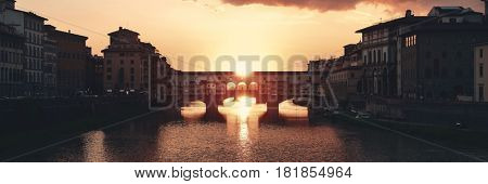 Ponte Vecchio over Arno River panorama in Florence Italy at sunset moment.
