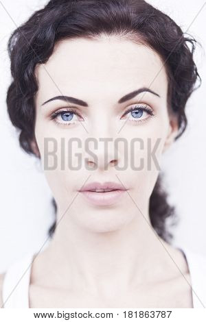 Curly noble blue-eyed woman. Clouse up portrait