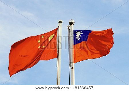 Mainland China And Taiwan Flag Waving Over Blue Sky