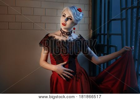 Woman with a vampire fangs in a red dress.