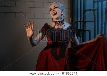 Woman in red dress with vampire grin Victorian style.