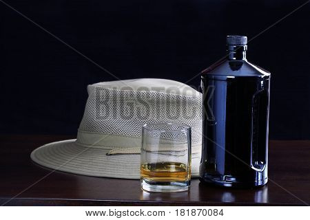 A bottle of whiskey a glass of whiskey and a hat on the bar