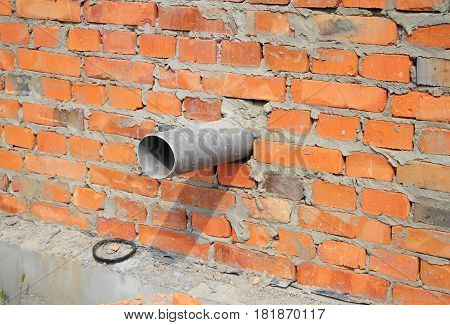 House brick wall over sewer pipe drainage system.